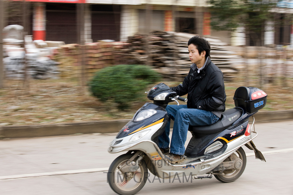 Man on a scooter in road near Guilin, China