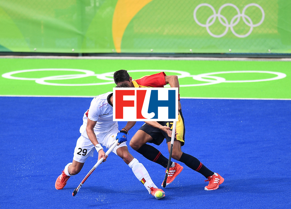 Belgium's Elliot van Strydonck (L) vies for the ball with Spain's Xavi Lleonart during the men's field hockey Spain vs Belgium match of the Rio 2016 Olympics Games at the Olympic Hockey Centre in Rio de Janeiro on August, 11 2016. / AFP / MANAN VATSYAYANA        (Photo credit should read MANAN VATSYAYANA/AFP/Getty Images)