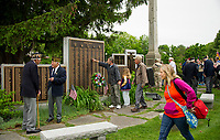A family shares a moment at the World War II Memorial in Veteran's Square following the Memorial Day parade and service on Monday morning.  (Karen Bobotas/for the Laconia Daily Sun)