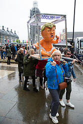 London, UK. 4 June, 2019. Activists carry a figure of President Trump in a cage during a protest by thousands of climate change activists, women's groups, students, pacifists, trade union members and families against the state visit of US President Donald Trump on the second day of his three day visit. A large policing operation was in place to facilitate the protest but to prevent access to areas immediately adjacent to Downing Street, where talks were taking place between Prime Minister Theresa May and President Trump.