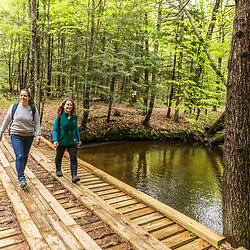 Two women walk  on a bridge crossing Mill Brook in Westbrook, Maine.