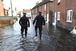 Two policeman struggle through a flooded street in the village of Bridge, Kent , United Kingdom. Sunday, 9th February 2014. Picture by Stephen Lock / i-Images