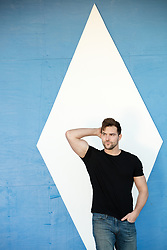 All American man against a blue wall with a diamond