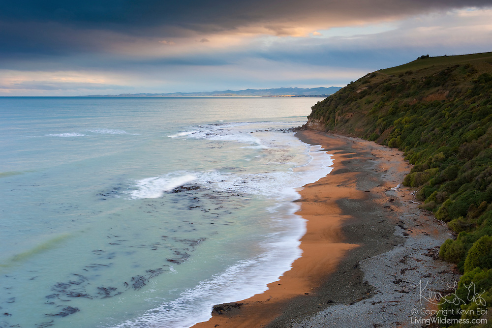 Red clouds at sunset hover over the red sand of Bushy Beach, located near Oamaru, New Zealand. The beach is famous for its yellow-eyed penguin colony.