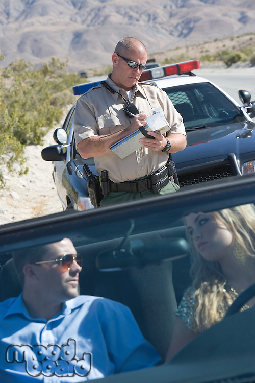 Policeman writing speeding ticket for couple