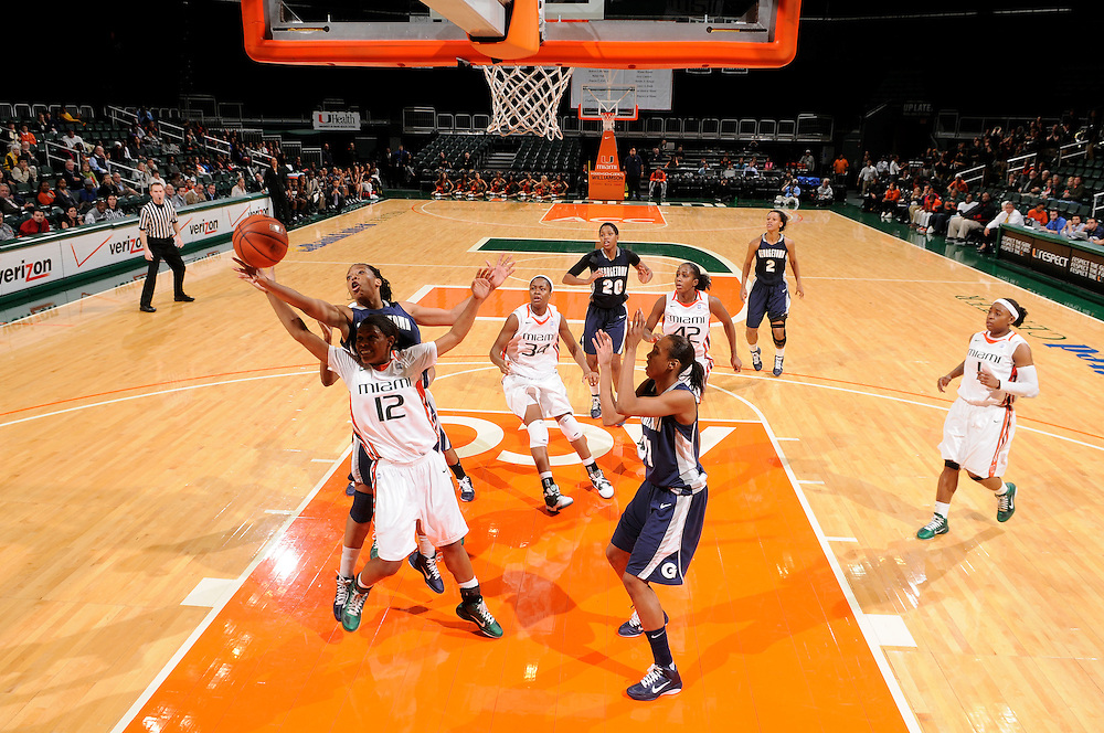 December 7, 2010: Morgan Williams (far left) of the Georgetown Hoyas reaches over Krystal Saunders (12) of the Miami Hurricanes for a rebound during the NCAA basketball game between Georgetown and Miami. The 'Canes defeated the Hoyas 81-72.