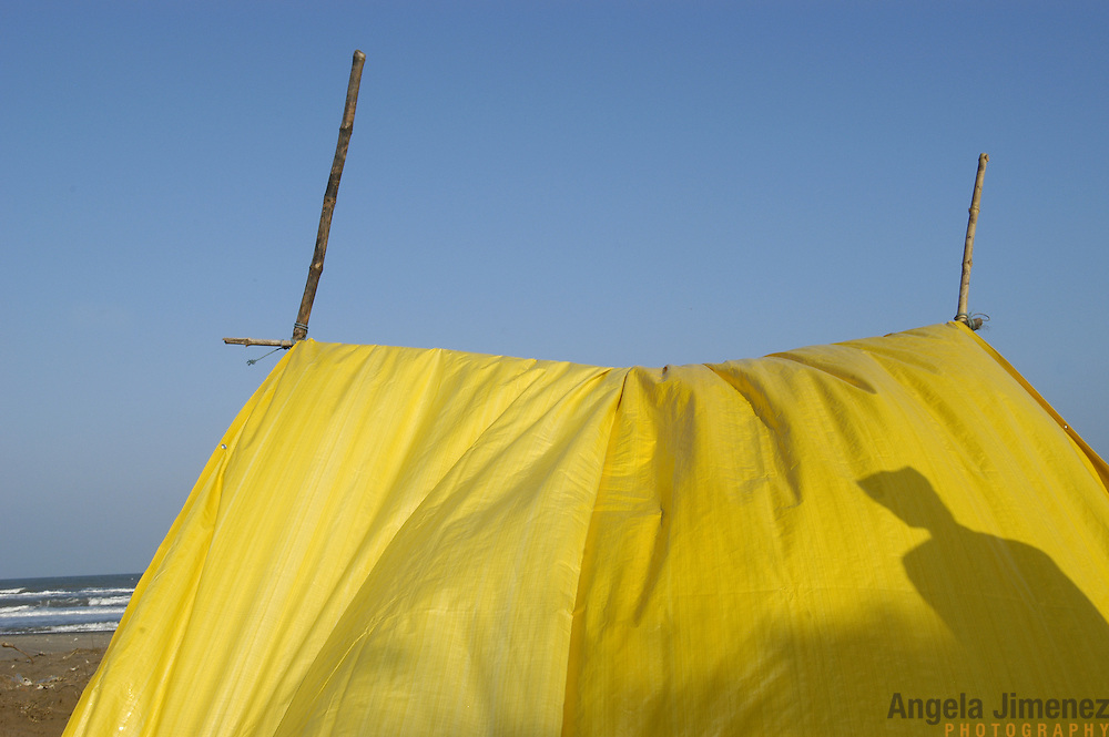 A fisherman sets up a government-issued tarp on the spot where his home used to stand next to the ocean as residents await the reconstruction of permanent shelter in Perumalpettai, a fishing village in Tamil Nadu, India, on January 15, 2005, after the area was struck by the Indian Ocean Tsunami on December 26, 2004, killing 37 of the villagers and destroying nearly all of their fishing boats. Generated by an earthquake on the ocean floor, the tsunami devastated the fishing industry along the southeastern coast of India.