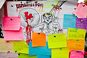 "07 MAY 2010 - BANGKOK, THAILAND: Notes left by the Red Shirts on a wall in Ratchaprasong Intersection call for Thai Prime Minsiter Abhisit Vjjajiva to step down frame a caricature of the Prime Minister as Hitler with Thai blood coming off his hands. Red Shirt protestors in Ratchaprasong intersection, Friday May 7, more than one month after the Reds occupied the intersection. Members of the United Front of Democracy Against Dictatorship (UDD), also known as the ""Red Shirts"" and their supporters moved their anti government protests into central Bangkok Apr. 4 when they occupied Ratchaprasong intersection, the site of Bangkok's fanciest shopping malls and several 5 star hotels. The Red Shirts are demanding the resignation of current Thai Prime Minister Abhisit Vejjajiva and his government. The protest is a continuation of protests the Red Shirts have been holding across Thailand. They support former Prime Minister Thaksin Shinawatra, who was deposed in a coup in 2006 and went into exile rather than go to prison after being convicted on corruption charges. Thaksin is still enormously popular in rural Thailand. This move, away from their traditional protest site in the old part of Bangkok, has gridlocked the center of the city and closed hundreds of stores and restaurants and several religious shrines.     PHOTO BY JACK KURTZ"
