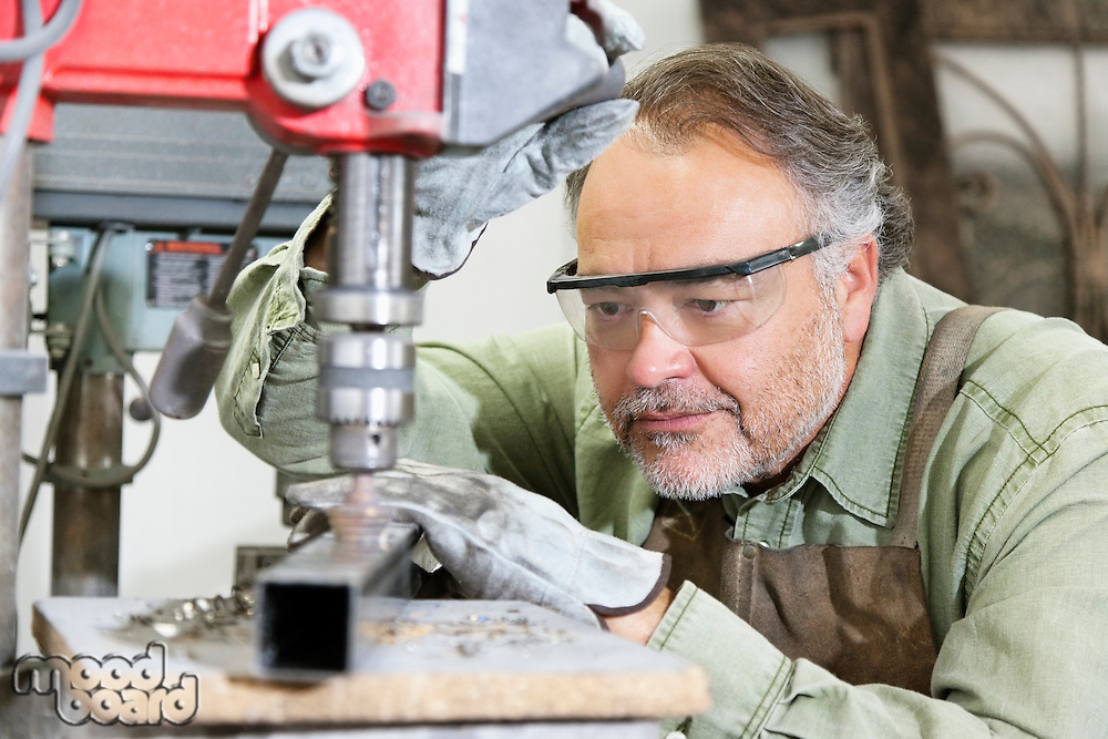 Mature man wearing protective eyewear while working with machinery in workshop