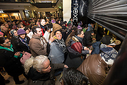 © Licensed to London News Pictures . 26/12/2013 . Manchester , UK . Crowds push to get in to Next in Manchester's Arndale Centre as the shutter opens . Queues for Next in Manchester's Arndale Centre stretch around the block , ahead of a 6am opening . Thousands of shoppers queue for hours in freezing temperatures in Manchester this Boxing Day morning (26th December 2013) in order to be amongst the first to purchase reduced price products in shops' sales . Photo credit : Joel Goodman/LNP
