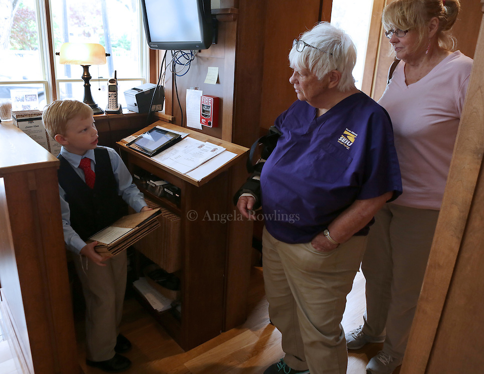 (Falmouth, MA - 5/28/15) Charlie Rickard, 8, who works weekends as a maitre d' in his parents' Falmouth restaurant, Bear in Boots, greets guests Carole[cq] Spear of Falmouth, center, and Jill Braceland of Waterville, Maine, Thursday, May 28, 2015. He says he is better on the computer than his mom, so he is able to update the tables quickly, and he enjoys talking with people. Staff photo by Angela Rowlings.