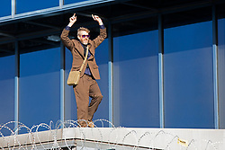 © Licensed to London News Pictures. 10/10/2019. London, UK. An Extinction Rebellion activist dances on top of London City airport on the fourth day of protests . Photo credit: George Cracknell Wright/LNP