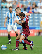 Picture by Graham Crowther/Focus Images Ltd. 07763140036.10/9/11 .Donal McDermott of Huddersfield and John Welsh of Tranmere tangle for the ball during the Npower League 1 game at the Galpharm Stadium, Huddersfield.