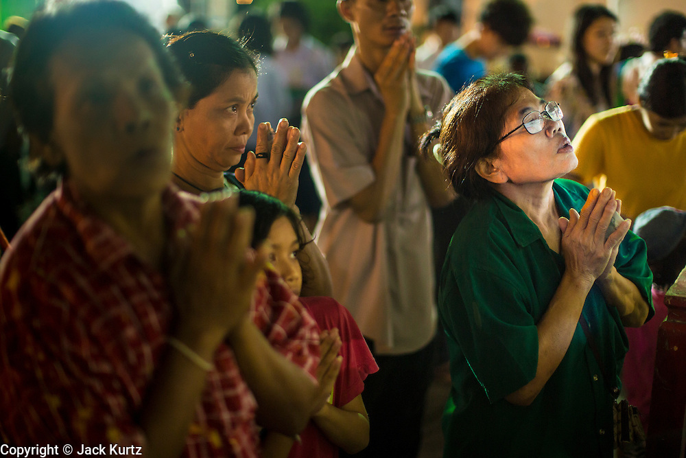 28 NOVEMBER 2012 - BANGKOK, THAILAND: People pray during Loy Krathong ceremonies at Wat Yannawa in Bangkok. Loy Krathong takes place on the evening of the full moon of the 12th month in the traditional Thai lunar calendar. In the western calendar this usually falls in November. Loy means 'to float', while krathong refers to the usually lotus-shaped container which floats on the water. Traditional krathongs are made of the layers of the trunk of a banana tree or a spider lily plant. Now, many people use krathongs of baked bread which disintegrate in the water and feed the fish. A krathong is decorated with elaborately folded banana leaves, incense sticks, and a candle. A small coin is sometimes included as an offering to the river spirits. On the night of the full moon, Thais launch their krathong on a river, canal or a pond, making a wish as they do so.    PHOTO BY JACK KURTZ