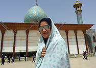 Iran, Fars Province, Shiraz, Iranian woman with fashionable sunglasses in front of a mosque.