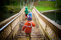 A boy walks across a bridge on the way to search for salamanders.