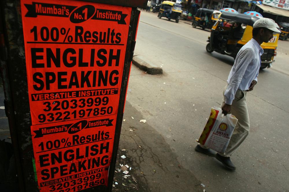 A man walks past advertisements of English Speaking classes displayed on a road, in Mumbai, India, on Monday August 20, 2007. Photographer: Prashanth Vishwanathan