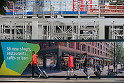 Pedestrians walk past a regeneration project hoarding at Elephant Park, at Elephant & Castle, London borough of Southwark. Southwark Council's development partner, Lendlease is regenerating over 28 acres across three sites at the heart of Elephant & Castle, in what is the latest major regeneration opportunity in zone 1 London. The vision for the £1.5 billion regeneration is to build on the area's strengths and vibrant character in order to re-establish Elephant & Castle as one of London's most flourishing urban quarters. The Elephant & Castle regeneration is of a scale rarely seen in central London and includes almost 3,000 new homes, plus office, retail, community, leisure and restaurant space.