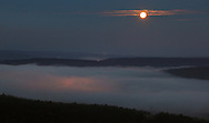 Greenville, New York  - The full moon sets over fog covering the Neversink and Delaware valleys on  Dec.10, 2011. The glow beneath the fog is from the lights of Port Jervis. ©Tom Bushey / The Image Works