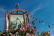 An image of  Jesuschrist on top of some kind of altar of flowers in the street due to the celebration of the of the Virgin of Guadalupe in  Manzanillo, Mexico.