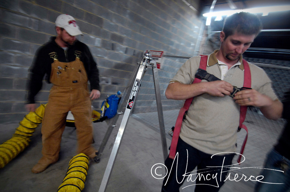 Students in an electrical apprenticeship classs practice safety procedures for working underground. Student Erik Harley puts on the harness that electrical workers must wear underground in case they need to be lifted out. There are conduits for elecrtical cable in the background.