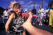 """Footography: Photograph of my right foot holding a hot pink comb toward the coyish spiked Mohawk hairstyle of a young """"punk"""" woman in San Francisco's Fisherman's Wharf area..©Rich Frishman"""