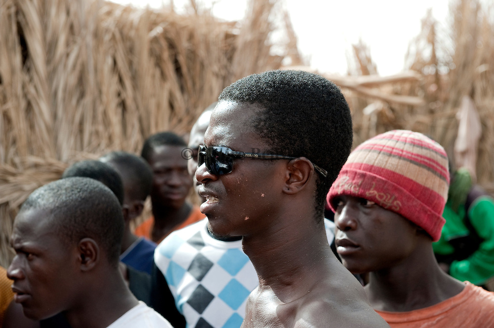 Emmanuel a young African migrant from Guinea Conakry listenning to a argument between Malians migrants and migrants from Burkina Fasoin a ghetto in Dirkou.