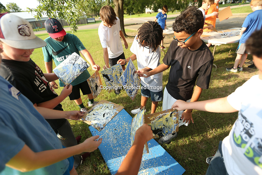 A group of Tupelo boys enrolled in the Junior Auxiliary WAVE program let the paint drip off their canvas onto another during a doulbe drip paint activity that was led by Tupelo Artist William Heard on Wednesday night at the Tupelo Police Athletic League. WAVE is a weeklong summer camp where boys are encouraged to participate in activites which promote high self-esteem, positive attitudes and healthier bodies ans minds.