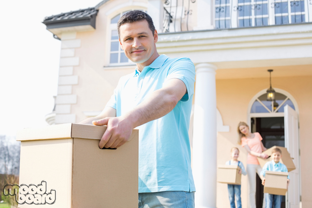 Portrait of confident man carrying cardboard box while moving house with family in background