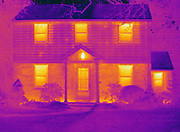 A thermogram of a home in winter. The temperature range goes from hot (white) to cold (blue). Thermography is a technique for visualizing the temperature of surfaces by recording the emission of long-wavelength infrared radiation. This heat radiation is detected electronically and displayed with different colors representing different temperatures.  In this image the whiter colors are the hottest.  The windows in homes are a major source of heat loss.
