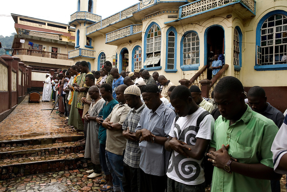 After 1 o'clock prayers in the mosque the day following her death, sheik suleiman Said Mansaray leads prayers to Mommy outsides the central mosque, while the women wait on the other side of the wall. Mommy delivered and died from postpartum bleeding in Freetown, Sierra leone.