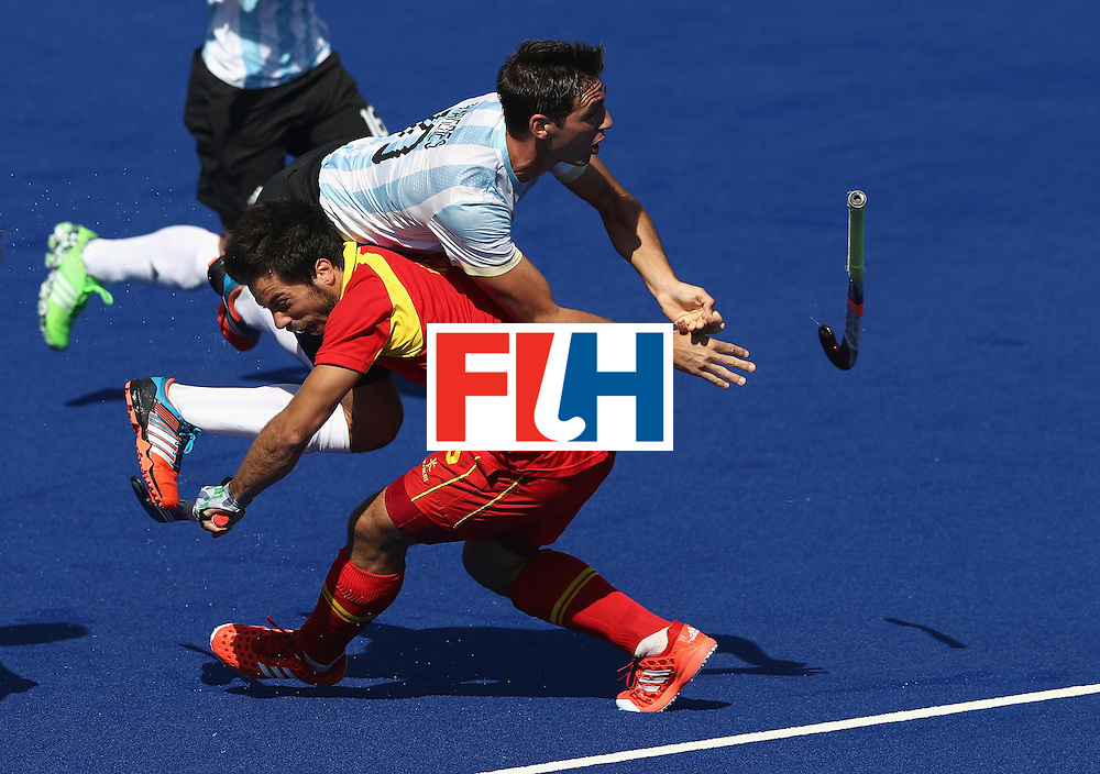 RIO DE JANEIRO, BRAZIL - AUGUST 14:  Matias Paredes of Argentina is brought down by Miguel Delas during the Men's hockey quarter final match between Spain and Argentina on Day 9 of the Rio 2016 Olympic Games at the Olympic Hockey Centre on August 14, 2016 in Rio de Janeiro, Brazil.  (Photo by David Rogers/Getty Images)