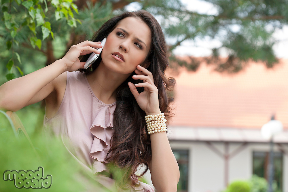 Beautiful young woman using cell phone in park