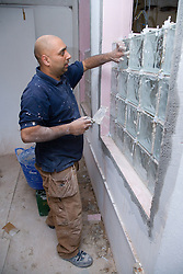 Man constructing glass brick window,