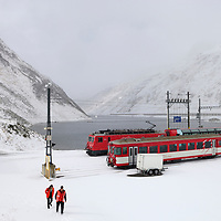 Oberalp train station at the summit of the Oberalp Pass (2044 m) in winter snow shortly before the pass road link, between Uri and Graubunden Cantons  closes for months in Winter. The railway line stays open, and as the line is single track, the station is an important crossing point.The area belonged to the National Redoubt, the final Swiss line of defence in the high alps, and is checkered with the remains of millitary installations, many of them underground, still camouflaged. The source of the Rhine is close by.