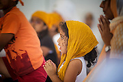 12 AUGUST 2012 - PHOENIX, AZ:  A girl prays during Sunday services at the Guru Nank Dwara Ashram Sikh temple in central Phoenix. Guru Nank Dwara Ashram is the oldest of three Sikh temples in the Phoenix area. There are about 1,500 Sikh families in the area. Memorials have been held throughout the week to honor the Sikhs killed in the mass shooting in Wisconsin last week. Sunday's service included several mentions of the massacre and was attended by a number of people active in the Phoenix interfaith community.   PHOTO BY JACK KURTZ