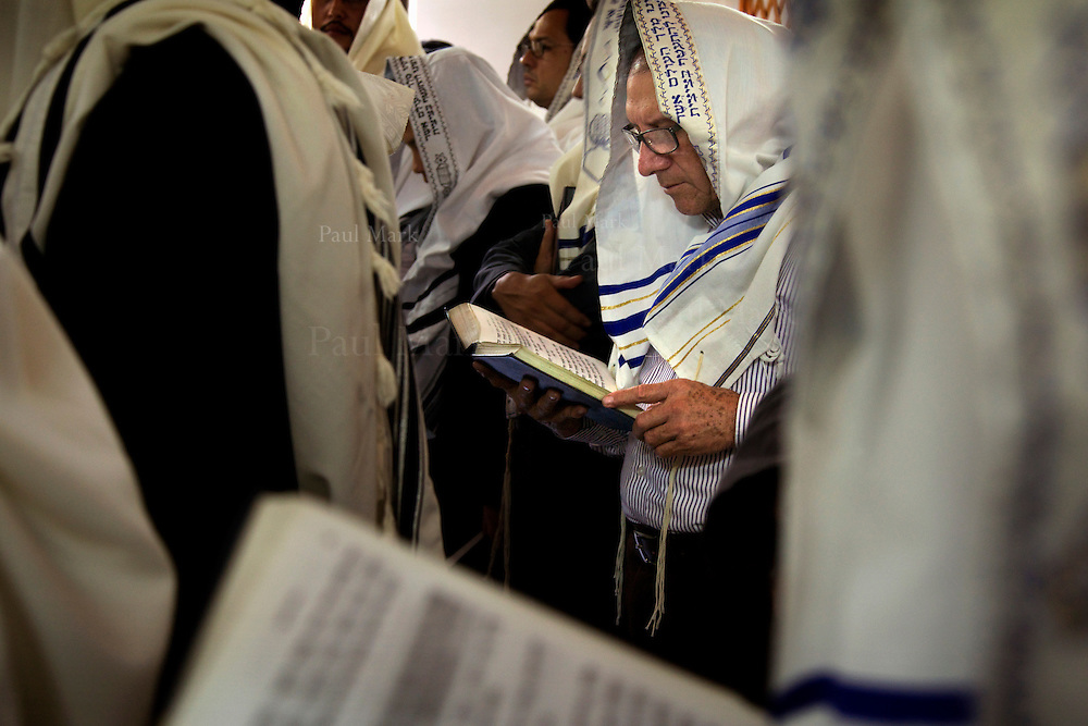 BELLO, COLOMBIA - November 4: A man worships in the synagogue in Bello, using a prayer book, the Siddur Birkat Shelomo, in which Spanish, Hebrew and phonetic versions are offered.