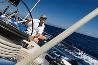 Sailor at helm of yacht on ocean