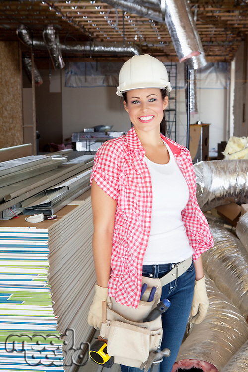 Portrait of a happy young woman architect wearing hardhat at construction site