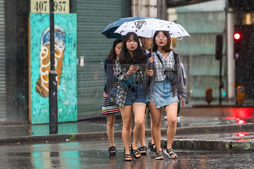 © Licensed to London News Pictures. 27/07/2019. London, UK. Women wearing shorts and sandals walking near London Bridge station during heavy rain this morning. London and the UK are experiencing heavy rain and stormy weather today following the heatwave and record temperatures during the week. Photo credit: Vickie Flores/LNP
