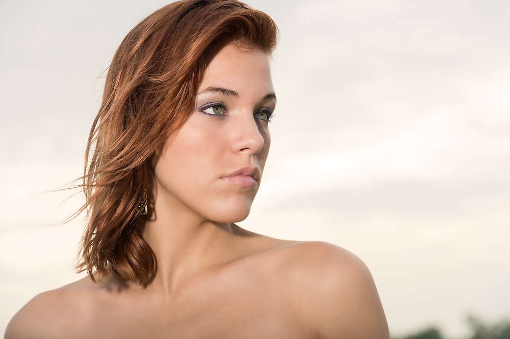 Portrait of red hair caucasian woman looking away outdoors