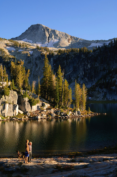 Couple and dog at Mirror Lake, Eagle Cap Wilderness, Wallowa Mountains, Oregon. (Eagle Cap Mountain above).
