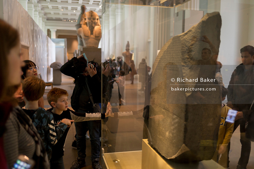 Visitors admire the Rosetta Stone in Room 4 of the British Museum, on 11th April 2018, in London, England.