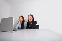 Bored young businesswomen using laptop at desk in office