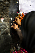 "18th December 2014, New Delhi, India. Women press coins onto a wall as  offerings and ask for wishes to be granted by Djinns in the ruins of Feroz Shah Kotla in New Delhi, India on the 18th December 2014<br /> <br /> PHOTOGRAPH BY AND COPYRIGHT OF SIMON DE TREY-WHITE a photographer in delhi<br /> + 91 98103 99809. Email: simon@simondetreywhite.com<br /> <br /> People have been coming to Firoz Shah Kotla to leave written notes and offerings for Djinns in the hopes of getting wishes granted since the late 1970's. Jinn, jann or djinn are supernatural creatures in Islamic mythology as well as pre-Islamic Arabian mythology. They are mentioned frequently in the Quran  and other Islamic texts and inhabit an unseen world called Djinnestan. In Islamic theology jinn are said to be creatures with free will, made from smokeless fire by Allah as humans were made of clay, among other things. According to the Quran, jinn have free will, and Iblis abused this freedom in front of Allah by refusing to bow to Adam when Allah ordered angels and jinn to do so. For disobeying Allah, Iblis was expelled from Paradise and called ""Shaytan"" (Satan).They are usually invisible to humans, but humans do appear clearly to jinn, as they can possess them. Like humans, jinn will also be judged on the Day of Judgment and will be sent to Paradise or Hell according to their deeds. Feroz Shah Tughlaq (r. 1351–88), the Sultan of Delhi, established the fortified city of Ferozabad in 1354, as the new capital of the Delhi Sultanate, and included in it the site of the present Feroz Shah Kotla. Kotla literally means fortress or citadel."
