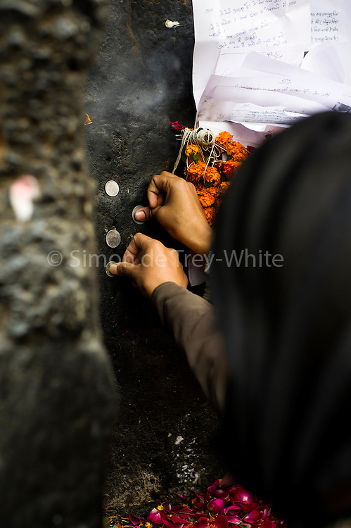 18th December 2014, New Delhi, India. Women press coins onto a wall as  offerings and ask for wishes to be granted by Djinns in the ruins of Feroz Shah Kotla in New Delhi, India on the 18th December 2014<br /> <br /> PHOTOGRAPH BY AND COPYRIGHT OF SIMON DE TREY-WHITE a photographer in delhi<br /> + 91 98103 99809. Email: simon@simondetreywhite.com<br /> <br /> People have been coming to Firoz Shah Kotla to leave written notes and offerings for Djinns in the hopes of getting wishes granted since the late 1970's. Jinn, jann or djinn are supernatural creatures in Islamic mythology as well as pre-Islamic Arabian mythology. They are mentioned frequently in the Quran  and other Islamic texts and inhabit an unseen world called Djinnestan. In Islamic theology jinn are said to be creatures with free will, made from smokeless fire by Allah as humans were made of clay, among other things. According to the Quran, jinn have free will, and Iblis abused this freedom in front of Allah by refusing to bow to Adam when Allah ordered angels and jinn to do so. For disobeying Allah, Iblis was expelled from Paradise and called &quot;Shaytan&quot; (Satan).They are usually invisible to humans, but humans do appear clearly to jinn, as they can possess them. Like humans, jinn will also be judged on the Day of Judgment and will be sent to Paradise or Hell according to their deeds. Feroz Shah Tughlaq (r. 1351&ndash;88), the Sultan of Delhi, established the fortified city of Ferozabad in 1354, as the new capital of the Delhi Sultanate, and included in it the site of the present Feroz Shah Kotla. Kotla literally means fortress or citadel.