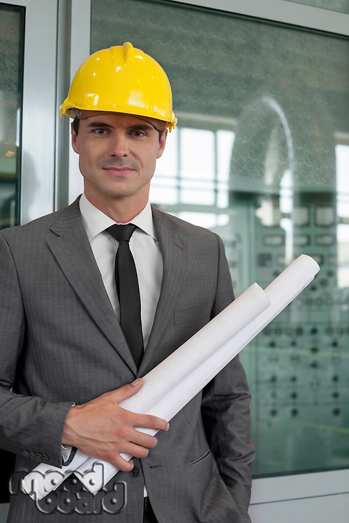 Portrait of confident young male architect holding blueprints in industry