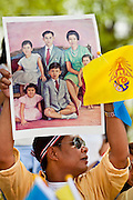 05 MAY 2010 - BANGKOK, THAILAND: A man holds up a family portrait of the Thai Royal Family, as the yellow Royal flag flies in front of him, as he waits for the King's motorcade, Wednesday, May 5. Wednesday was Coronation Day in Thailand, marking the 60th anniversary of the coronation of Thai King Bhumibol Adulyade, also known as Rama IX. He is the world's longest serving current head of state and the longest reigning monarch in Thai history. He has reigned since June 9, 1946 and his coronation was on May 5, 1950, after he finished his studies. The King is revered by the Thai people. Thousands lined the streets around the Grand Palace hoping to catch a glimpse of the King as his motorcade pulled into the palace. The King has been hospitalized since September 2009, making only infrequent trips out of the hospital for official functions, like today's ceremonies.   PHOTO BY JACK KURTZ