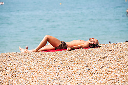 © Licensed to London News Pictures. 22/07/2016. Brighton, UK. Members of the public take to the beach in Brighton and Hove as hot and sunny weather continues to hit the seaside resort. Photo credit: Hugo Michiels/LNP