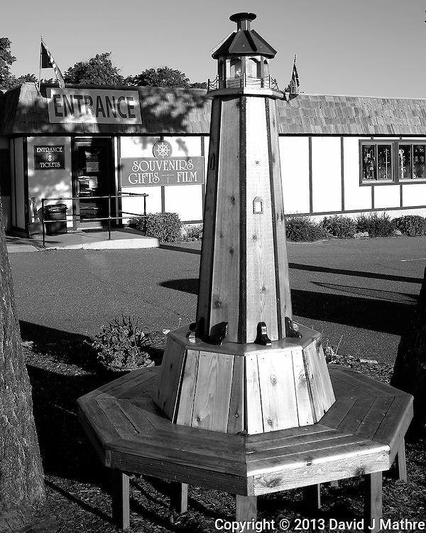 Lighthouse Bench Outside the Shop Selling Tickets to the Painted Rocks Lake Shore Cruise in Munising, Michigan. Image taken with a Leica X2 camera (ISO 100, 24 mm, f/2.8, 1/2000 sec). In camera B&W.